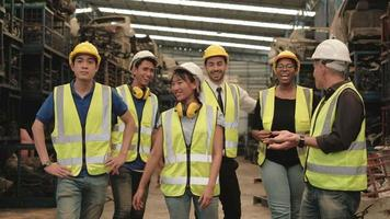 Various races workers and engineers of factory are having fun joking. video