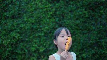 fille asiatique s'amusant en soufflant des bulles de savon joyeusement dans le jardin. video