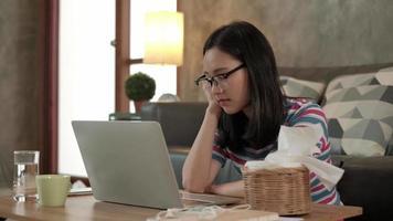 mulher asiática trabalhando em casa, cochilando e cochilando atrás de um laptop. video