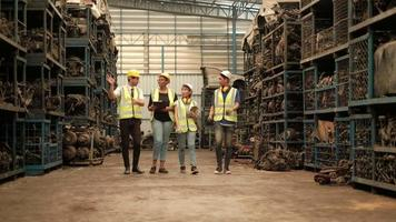 A group of people in safety uniforms and helmets in warehouse. video