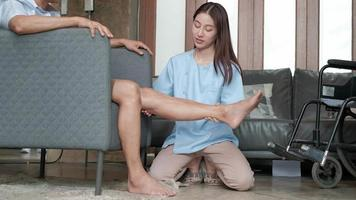 fisioterapeuta asiática rehabilitando a un hombre discapacitado. video