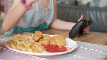 Child's eating fast food and forcing Joystick to play video games.