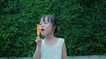 filles asiatiques s'amusant en soufflant joyeusement des bulles de savon dans le jardin. video