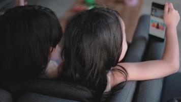 duas garotas de cabelo preto asiático sentadas em um sofá na sala de estar. video