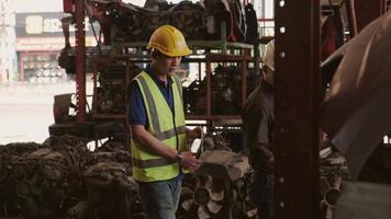deux ingénieurs masculins vérifiant les pièces du moteur dans un entrepôt. video