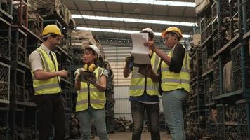 A group of engineers in safety uniforms in factory warehouse. video