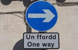 Right direction arrow sign. Un ffordd means One Way in Welsh. photo