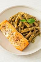 Pesto quadrotto penne pasta with grilled salmon photo
