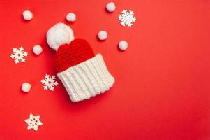 Christmas greeting card with red hat and snowflakes on red background photo