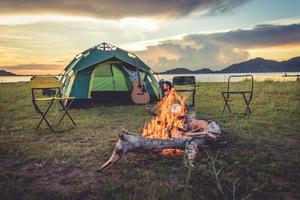 Camping tent with bonfire in the green field meadow photo