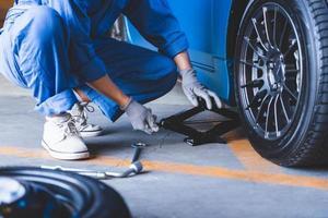 Mecánica de automóviles cambiando el neumático en el garaje del taller de reparación de automóviles foto