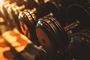 Mancuernas de acero negro en rack en el gimnasio deportivo foto