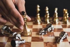 Hand moving golden chess figure eliminating in battle competition photo