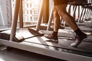 Close up of sport man running on treadmill in fitness gym photo