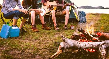 Travelers camping doing picnic and playing music in meadow field photo