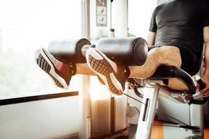 Cerca del hombre levantando pesas con las piernas para estirar en el gimnasio foto