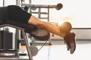 Cerca del deporte hombre estirando y levantando peso con dos piernas foto