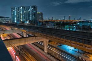 Sky train railway in metropolis in night life. Transportation concept. photo