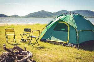 Camping tent with extinguished bonfire in the green field meadow photo