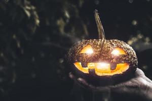 Halloween pumpkin in hand. Holiday and Religion concept photo