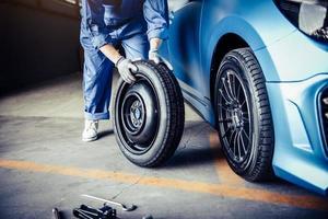 Car mechanics changing tire at auto repair shop garage photo