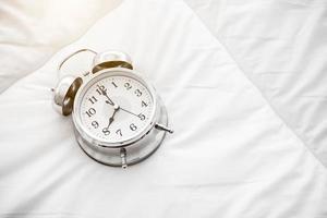 Suena el despertador en la sábana blanca foto