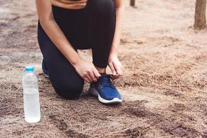 Woman tying up shoelaces jogging in forest with drinking water bottle photo