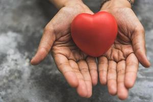 Close up female hands giving red heart as heart donor photo