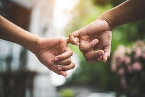 Close up couple holding pinkies fingers  in park as swear and promise photo