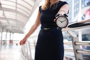 las mujeres de negocios muestran el despertador y se sorprenden con las horas punta foto