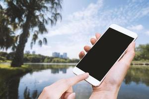Woman hold smart phone and touch button by hand with blank screen photo