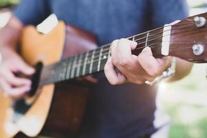 Close up of guitarist hand playing guitar photo