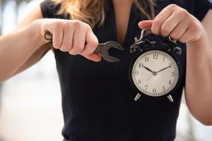 mujer de negocios, tratar de ajustar la hora, en, despertador foto