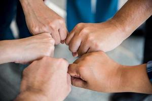 Close up top view of young people doing fist bump by hands together photo