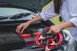 Primer plano de una mujer mano sujetando el cable de la batería para reparar el coche foto