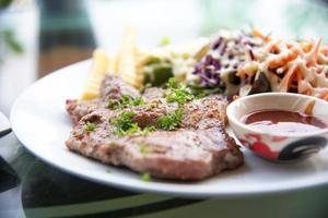 Pork chop steak with salad and gravy sauce in dish photo