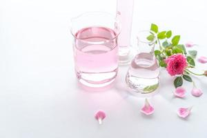 Tratamientos de spa rosa sobre mesa de madera blanca foto