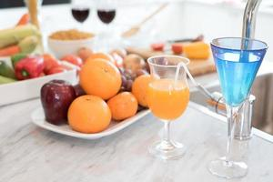 Fruit and fruit juice on marble counter in kitchen room photo