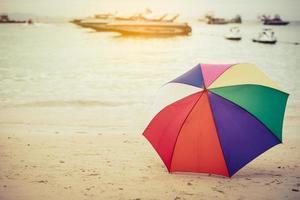 paraguas de colores del arco iris en la playa foto