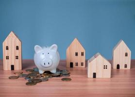 A white piggy bank is placed on a pile of coins. photo