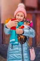 girl and chihuahua makes self portrait on smartphone in winter day photo