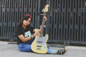 rock band cool girl portrait holding her bass guitar photo