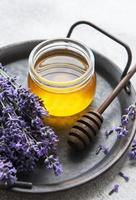 Jar with honey and fresh lavender flowers photo