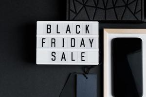 Black Friday sale. Smartphone and accessories on dark background. photo