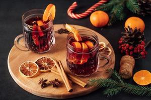 Two glasses of hot mulled wine with fruits on dark background. photo