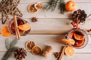 Hot mulled wine with fruits and spices on wooden background. photo