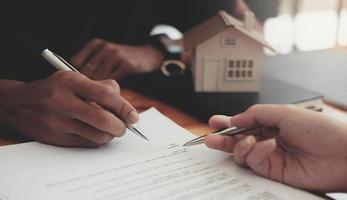 Cropped image of real estate agent assisting client to sign contractq photo
