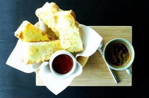 Cheesy Garlic Bread and black coffee drink on table backgrounds photo