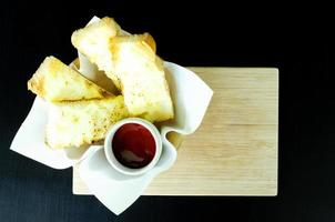 Cheesy Garlic Bread on wooden plate background above, copy space. photo