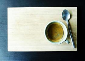 Hot coffee cups and spoon on wood plate backgrounds above photo